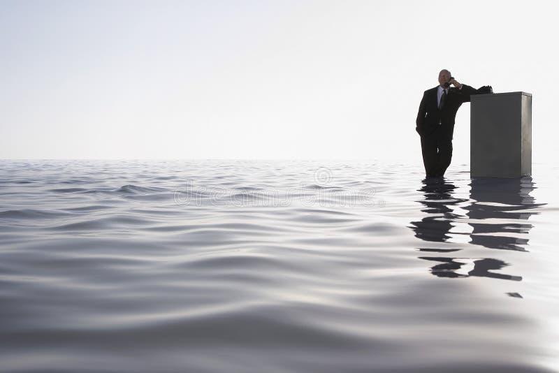 Affärsman Leaning On Cabinet, medan genom att använda telefonen i havet royaltyfria foton
