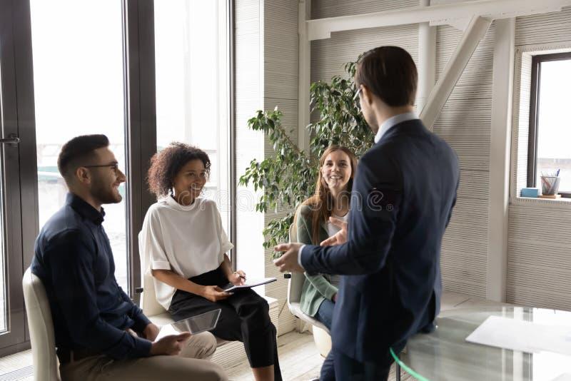 Affärsman leder möte med flera etniska medarbetare på kontoret arkivbilder