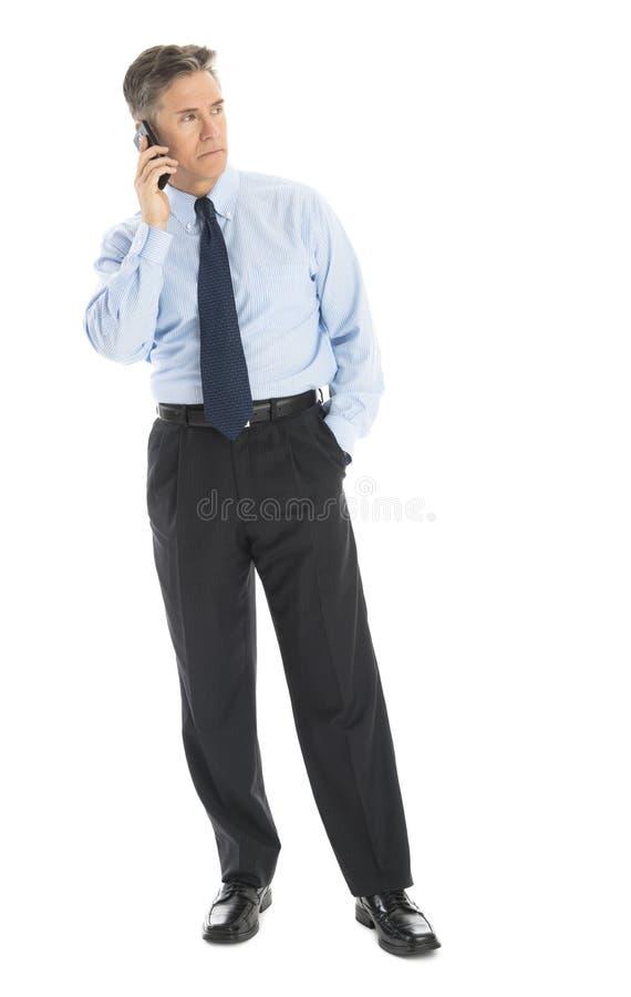 Affärsman Looking Away While som svarar den smarta telefonen royaltyfri bild