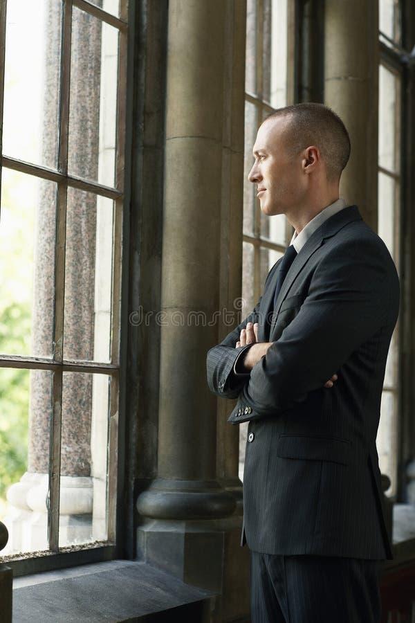Affärsman Looking Through Window arkivfoto