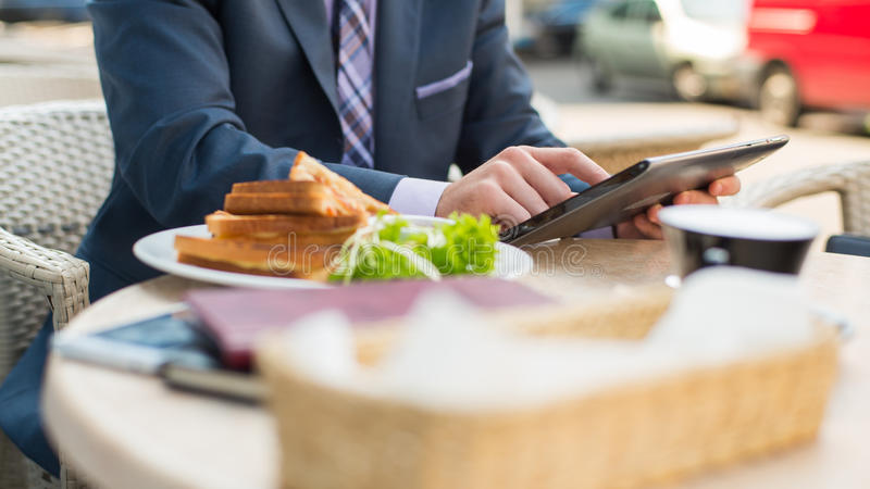 Affärsman med att surfa internet av minnestavlan under frukosten. arkivbilder