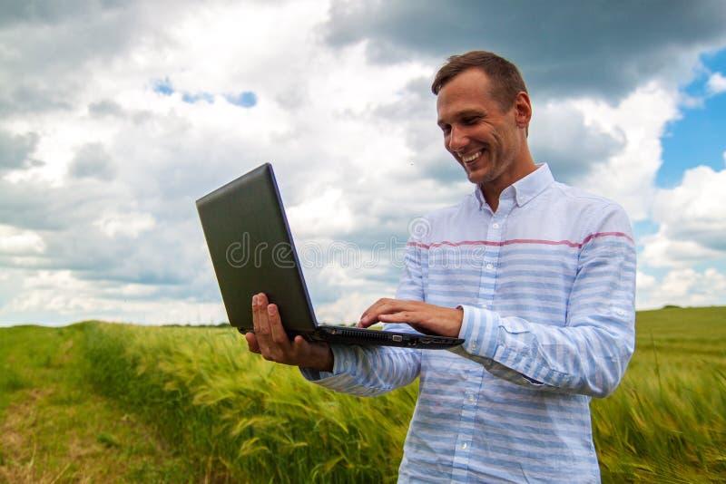 Affärsman med bärbar dator- och smartphonearbete i vetefält i bakgrund för blå himmel arkivbilder