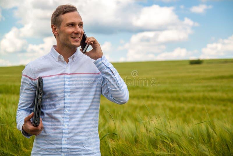 Affärsman med bärbar dator- och smartphonearbete i vetefält i bakgrund för blå himmel royaltyfria foton