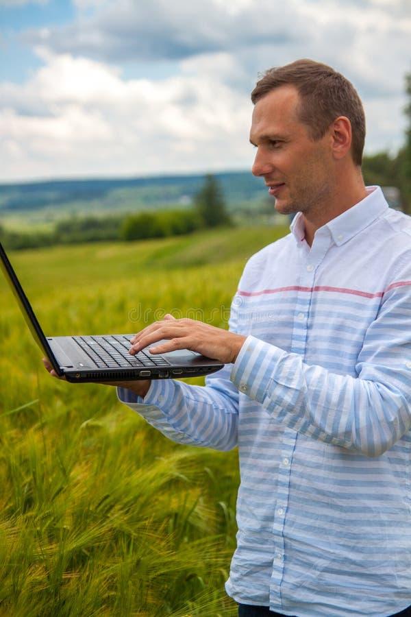 Affärsman med bärbar dator- och smartphonearbete i vetefält i bakgrund för blå himmel arkivfoton