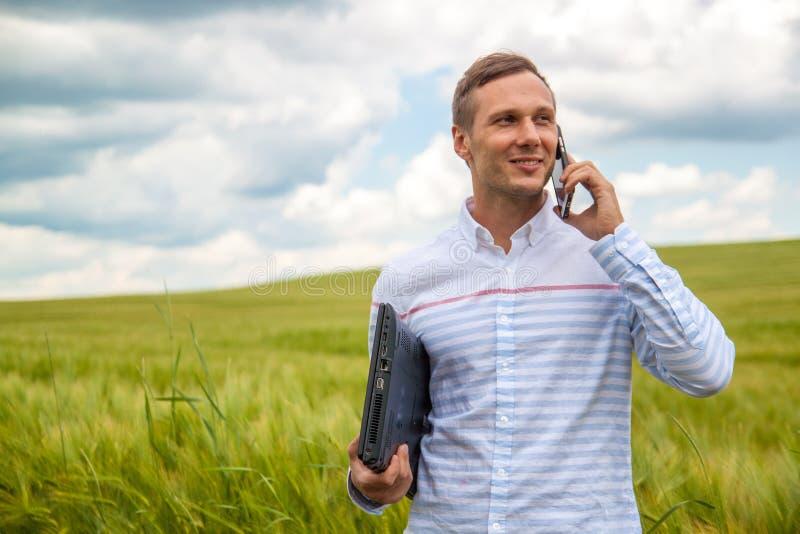 Affärsman med bärbar dator- och smartphonearbete i vetefält i bakgrund för blå himmel fotografering för bildbyråer