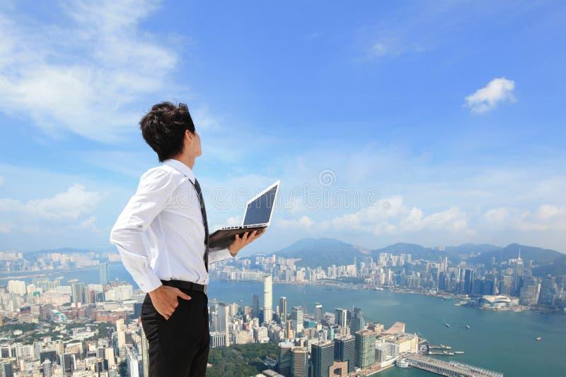 Affärsman med bärbara datorn och blick till staden arkivbilder
