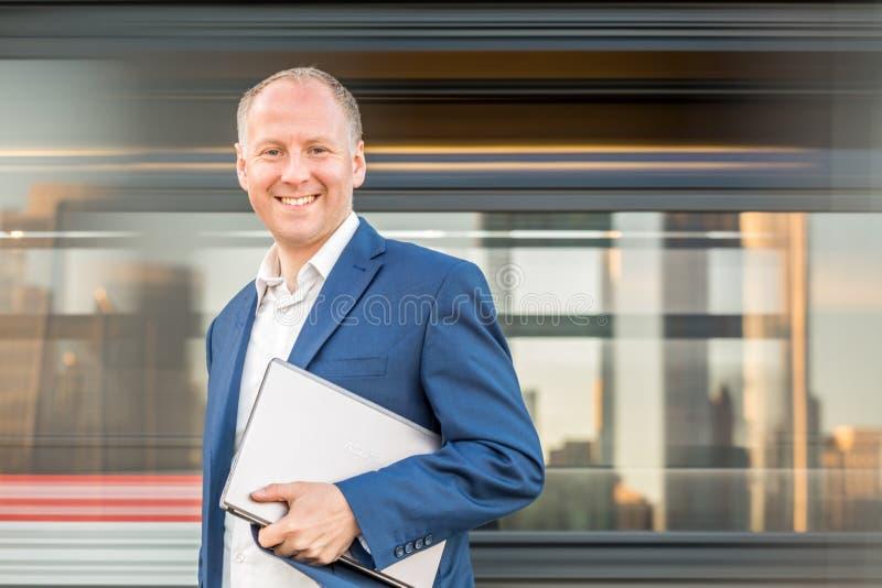 Affärsman med bärbara datorn på stads- bakgrund royaltyfri foto