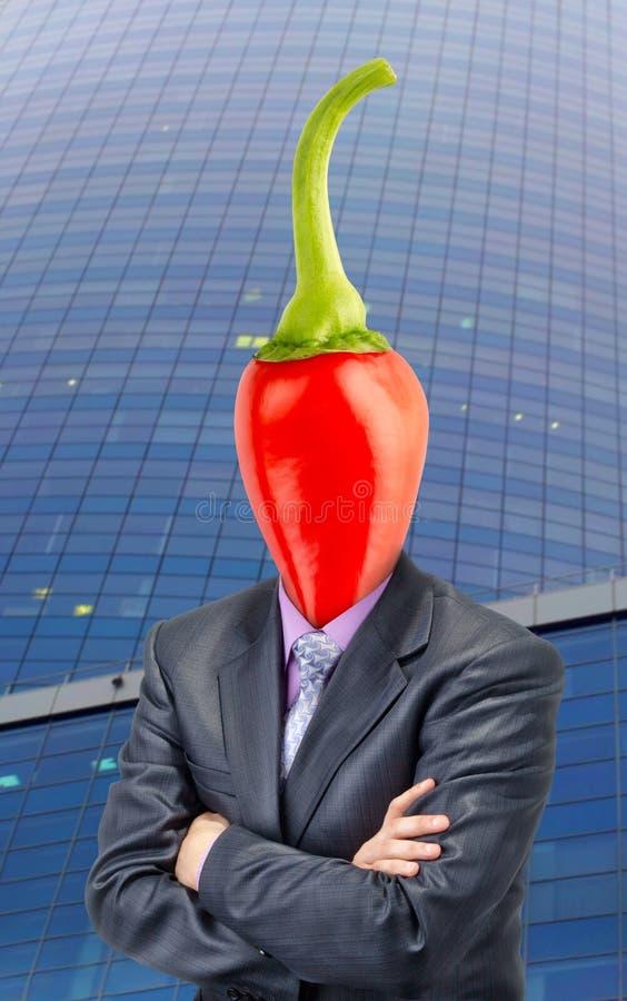 Affärsman med chilipeppar i stället för huvudet royaltyfria foton
