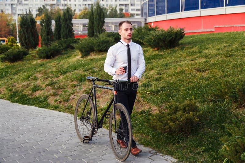 Affärsman med cykeln som dricker kaffe från tagande-bortkoppen royaltyfria bilder