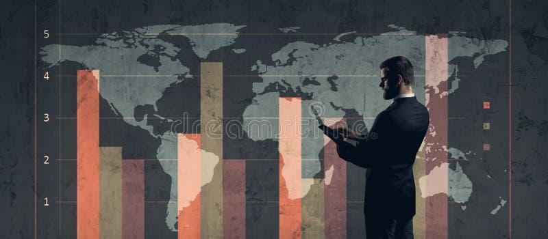 Affärsman med datorminnestavlan som står över diagram Världsmor arkivfoto