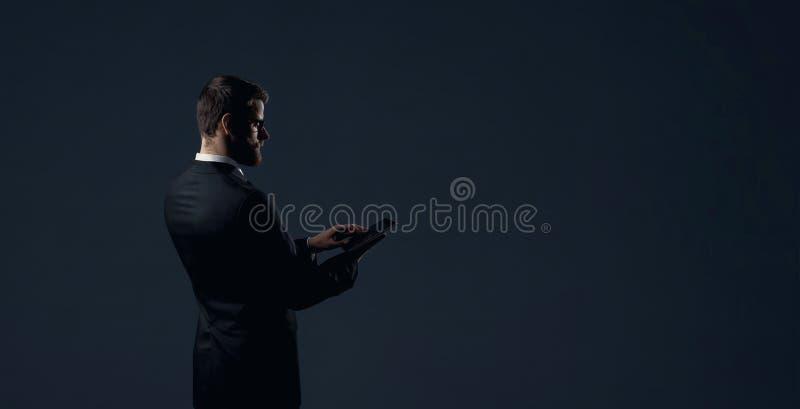 Affärsman med datorminnestavlan som står över svarta dramatiska lodisar arkivfoton