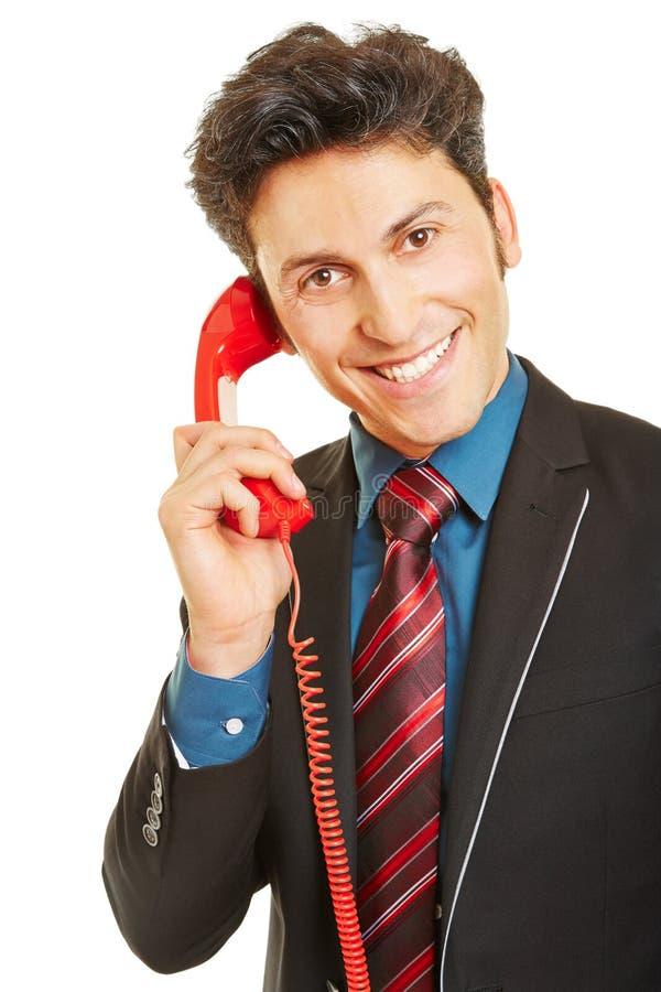 Affärsman med den röda telefonen royaltyfria bilder