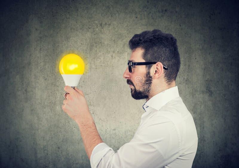 Affärsman med det fundersamma uttryckt som ser den ljusa ljusa kulan royaltyfria foton