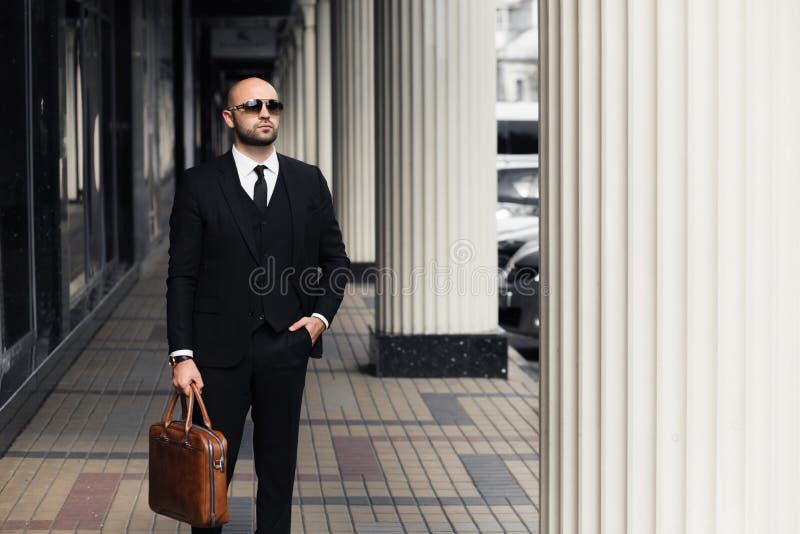 Affärsman med en brun påse nära kontoret arkivbilder
