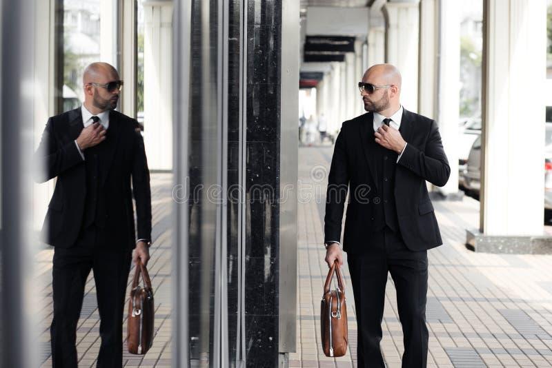 Affärsman med en brun påse nära kontoret arkivfoto