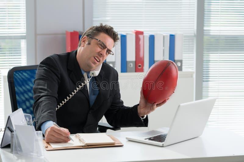 Affärsman med en fotboll arkivfoto