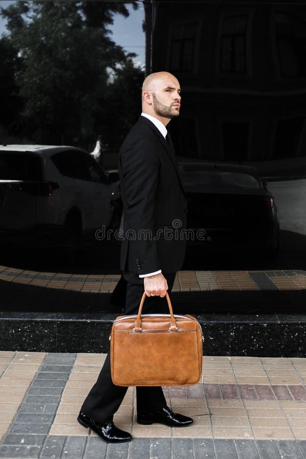 Affärsman med en påse nära kontoret royaltyfria bilder