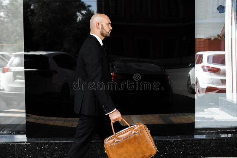 Affärsman med en påse nära kontoret arkivbild
