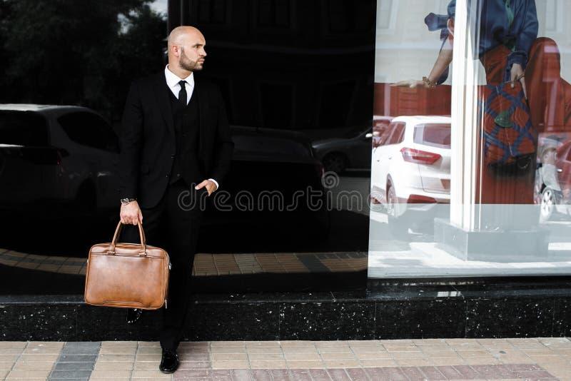 Affärsman med en påse nära kontoret royaltyfri fotografi