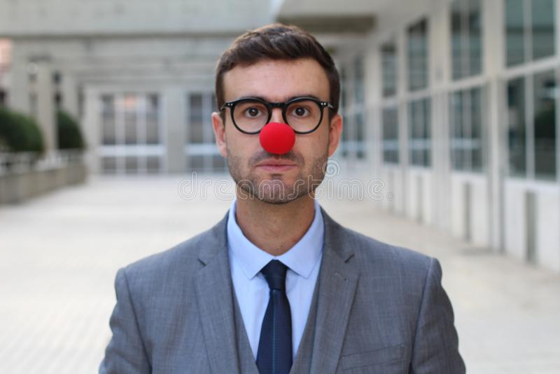 Affärsman med en röd clownnäsa arkivfoton