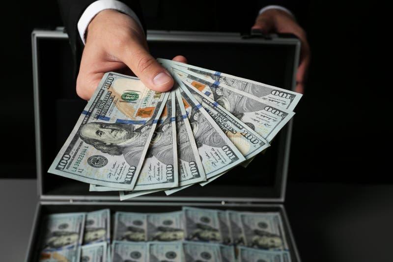 Affärsman med erbjudande pengar för resväska royaltyfria foton