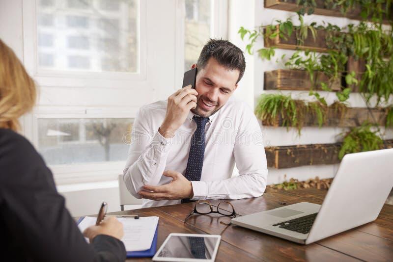 Affärsman med framställning av en appell och att arbeta på bärbara datorn, medan sitta i kontoret royaltyfri fotografi