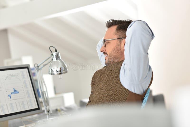 Affärsman med glasögon på kontoret som har ett avbrott royaltyfri foto