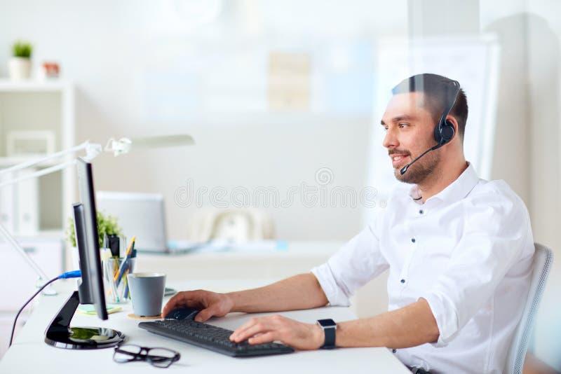 Affärsman med hörlurar med mikrofon och datoren på kontoret royaltyfri bild