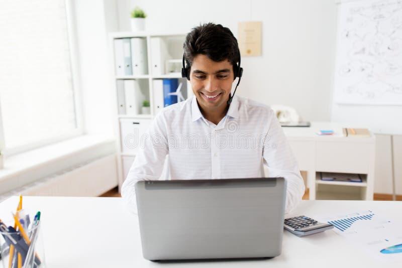 Affärsman med hörlurar med mikrofon och bärbara datorn på kontoret royaltyfria bilder