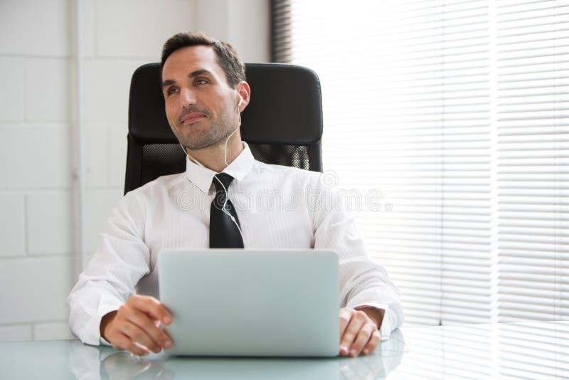Affärsman med hörlurar och bärbar datordatoren arkivfoton