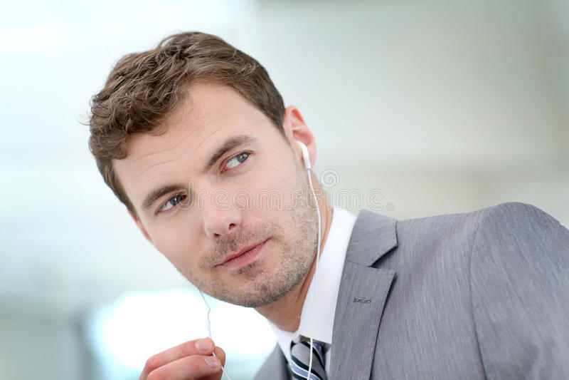 Affärsman med hörlurar som talar på telefonen royaltyfria foton