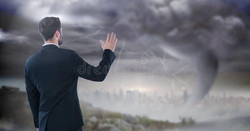 affärsman med handen upp i stormcityscape arkivfoto