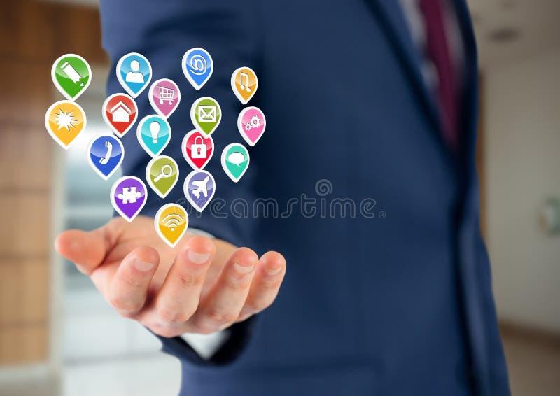 affärsman med handspridning av med applikationsymboler över Suddig bakgrund för kontor royaltyfri fotografi