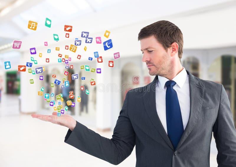 Affärsman med handspridning av med applikationsymboler som kommer upp form det Suddig kontorsbackgro arkivbilder