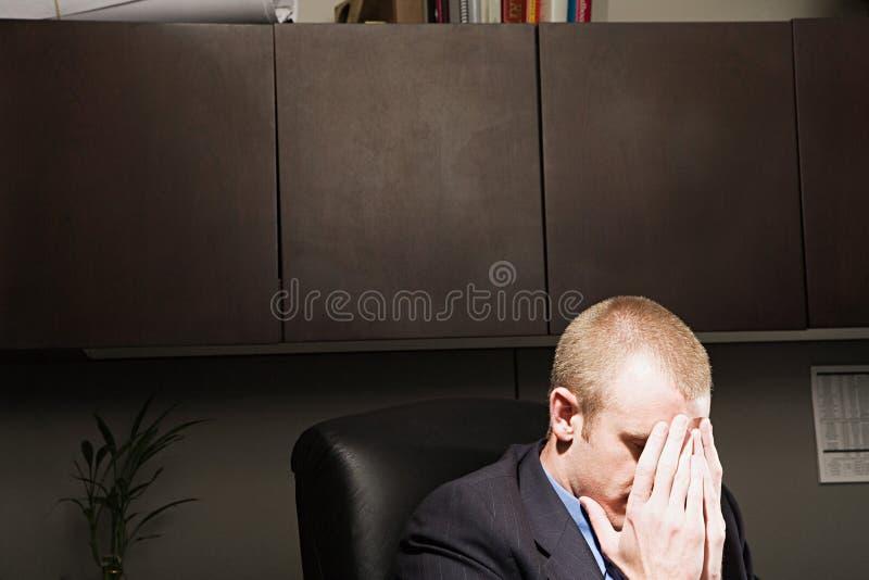 Affärsman med hans huvud i hans händer royaltyfria bilder