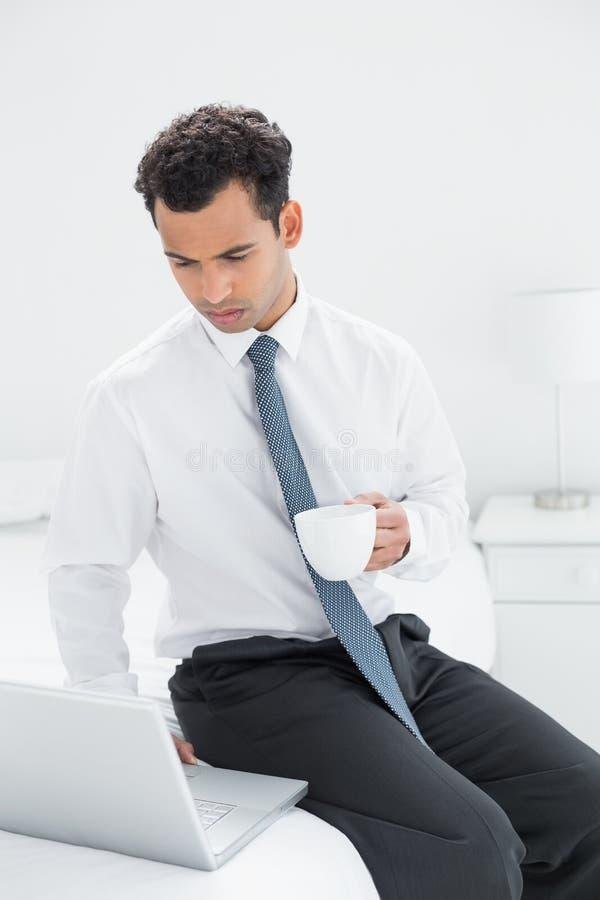 Affärsman med kaffekoppen genom att använda bärbara datorn på hotellrum fotografering för bildbyråer