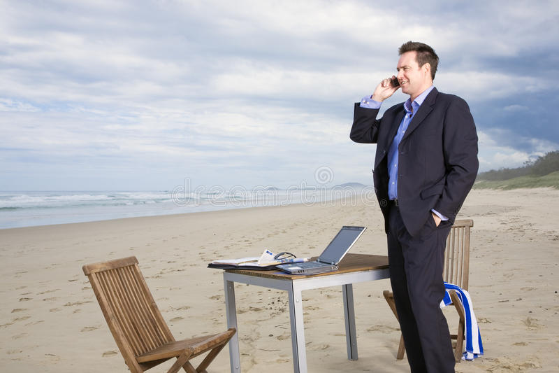 Affärsman med kontoret på stranden arkivfoton