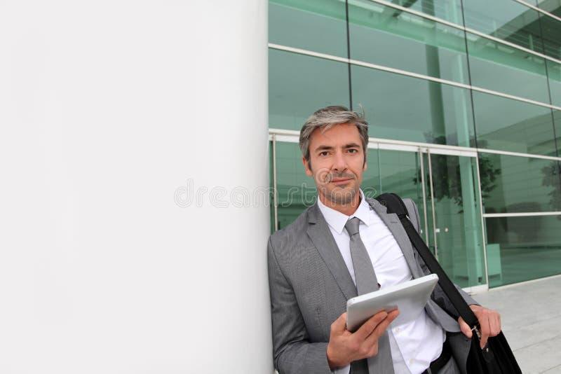 Affärsman med minnestavlan som lutar utomhus på väggen arkivfoto