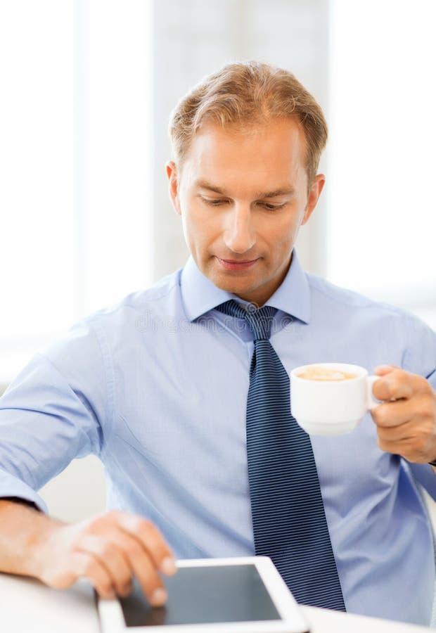 Affärsman med minnestavlaPC och kaffe i regeringsställning fotografering för bildbyråer