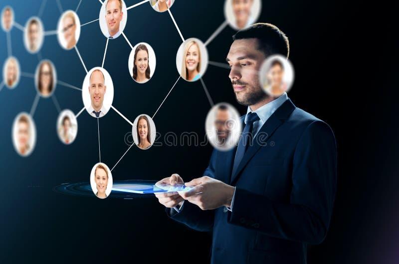 Affärsman med minnestavlaPC och kontaktnätverket arkivbild