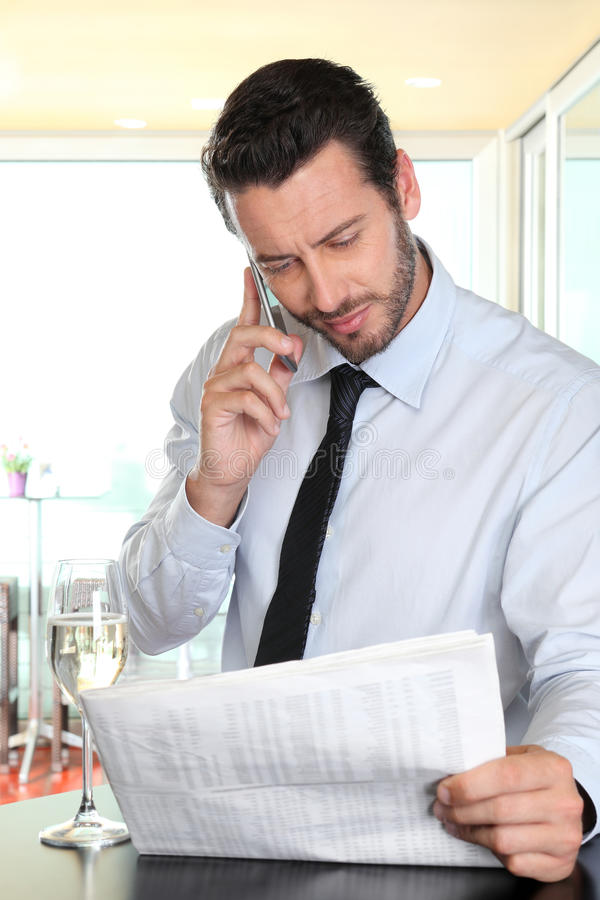 Affärsman med mobil läsning tidningen som stoppas på stången arkivbilder