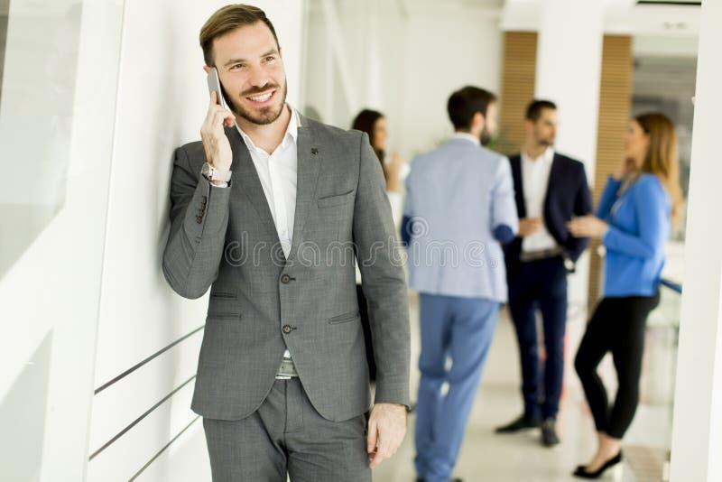Affärsman med mobiltelefonen i regeringsställning medan annan affärspeo arkivfoton