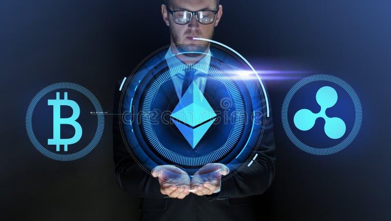 Affärsman med på cryptocurrencysymboler arkivbilder