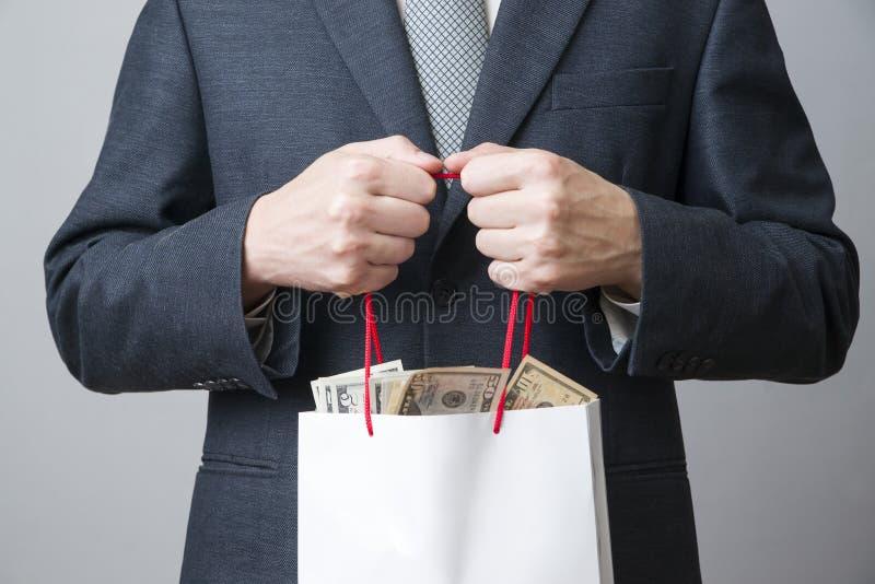 Affärsman med packen som är full av pengar i händerna av royaltyfria foton