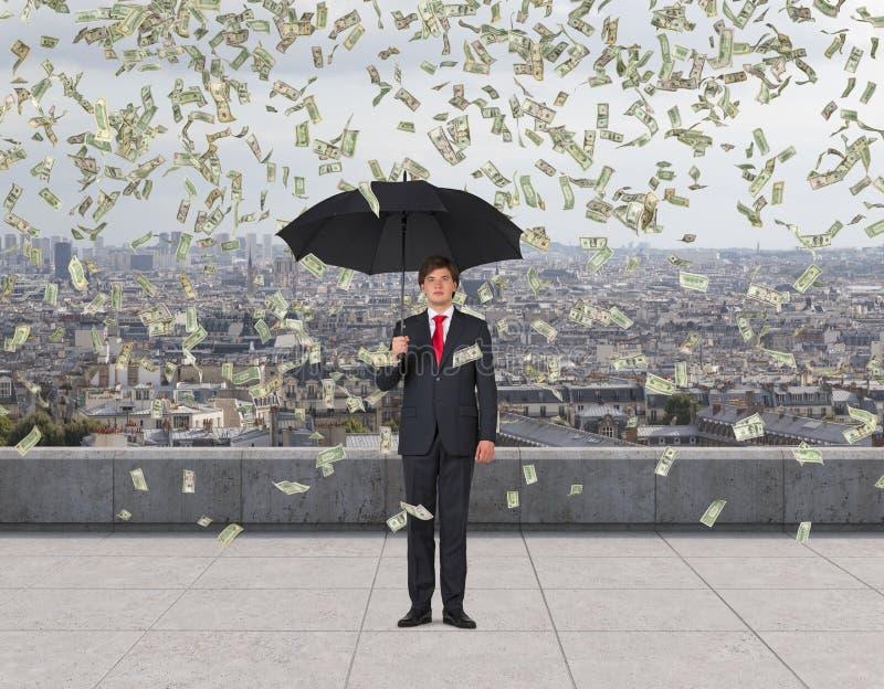 Affärsman med paraplyet och den fallande dollaren royaltyfri fotografi