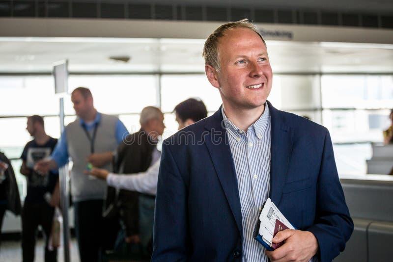 Affärsman med passet och logipasserande på flygplatsen fotografering för bildbyråer