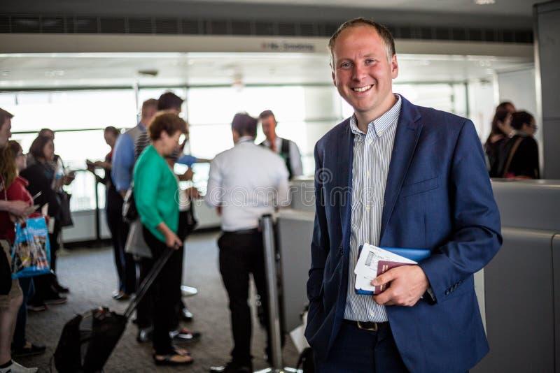 Affärsman med passet och logipasserande på flygplatsen royaltyfria foton