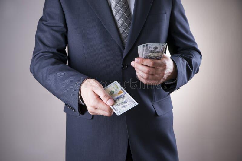 Affärsman med pengar i studio white för dollar för sedelbegreppskorruption isolerad kuvert arkivfoto