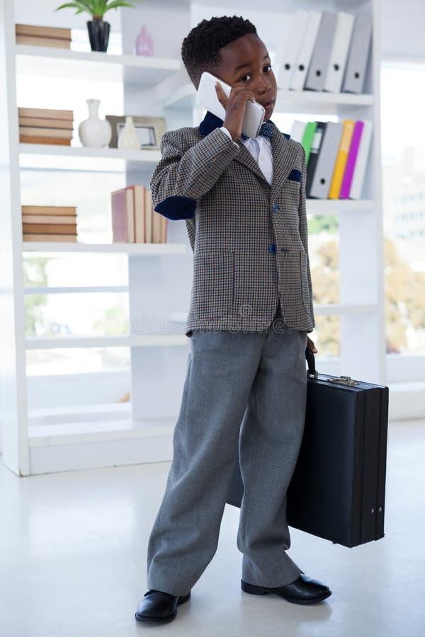 Affärsman med resväskan som talar på mobiltelefonen arkivfoto
