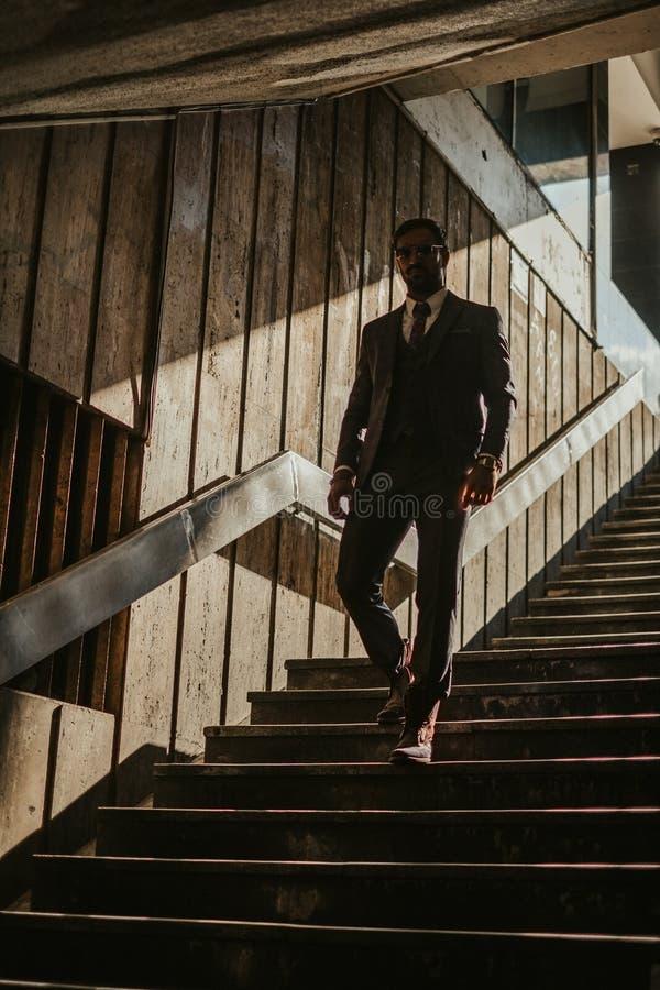 Affärsman med solglasögon som går ner trappan royaltyfria bilder